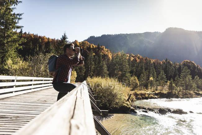 Austria, Alpi, uomo in un viaggio a piedi guardando attraverso binocoli — Foto stock