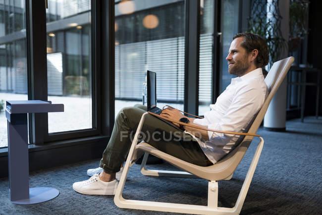 Uomo d'affari occasionale che lavora in area salotto di uno spazio di coworking, usando il computer portatile — Foto stock