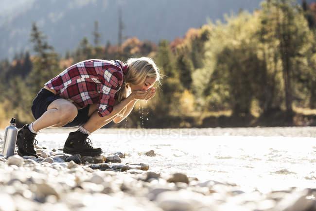 Austria, Alpes, mujer en un viaje de senderismo tomando un descanso en un arroyo - foto de stock