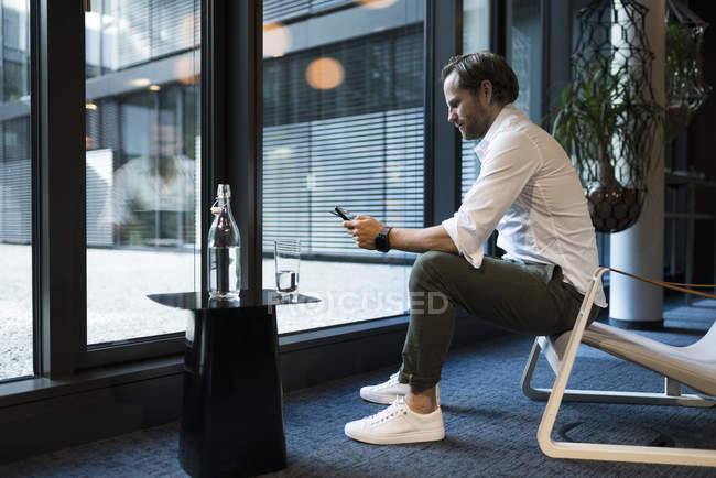 Casual businessman working in lounge area of a coworking space, using digital tablet — Stock Photo