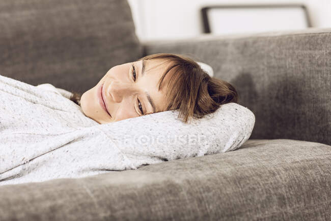 Mature woman relaxing on couch, daydreaming — Stock Photo