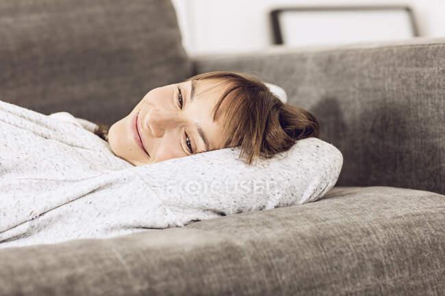 Зрелая женщина, расслабляясь на диване, мечтает — стоковое фото
