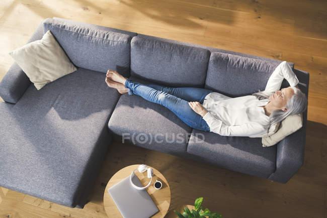 Старшая женщина отдыхает на диване — стоковое фото