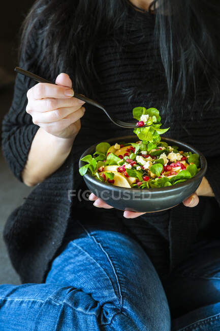 Woman eating mixed salad with lamb's lettuce, feta, pear, pomegranate seed and walnuts — Stock Photo