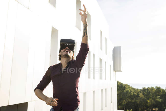 Man on a rooftop terrace, gaming with VR glasses — Stock Photo
