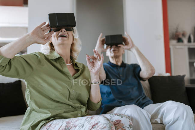 Happy senior couple at home sitting on couch wearing VR glasses — Stock Photo