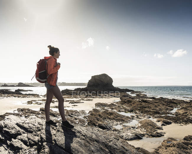 Young woman hiking on a rocky beach — Stock Photo