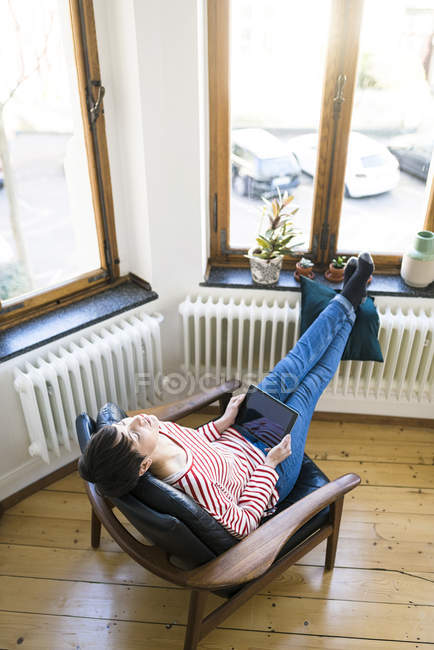 Short-haired woman relaxing in lounge chair holding tablet in stylish apartment — Stock Photo