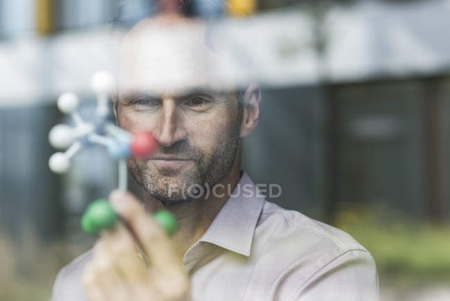Portrait of scientist with atomic model — Stock Photo