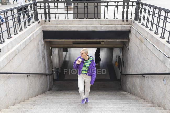 Молода жінка в барвистому одязі йде по сходах міста. — стокове фото
