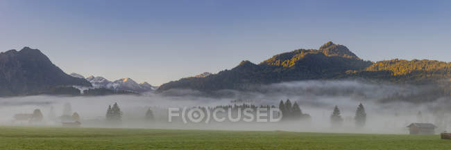 Germany, Bavaria, Upper Allgaeu, Loretto meadows near Oberstdorf with morning fog and mountains in background — Stock Photo