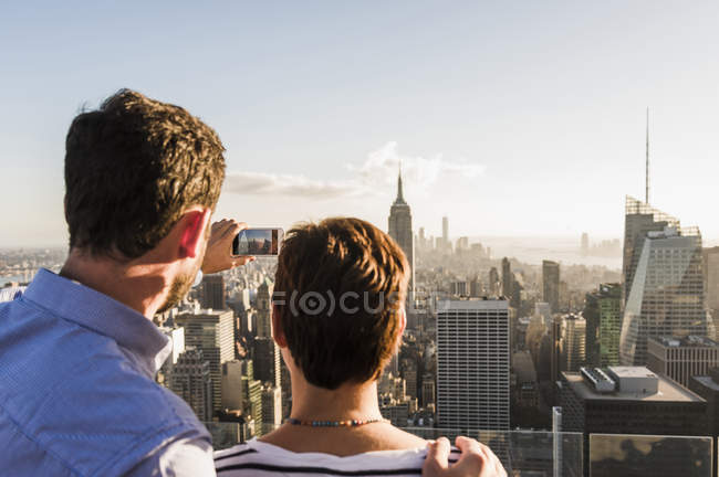 USA, New York, uomo con donna che scatta foto al cellulare sul ponte di osservazione del Rockefeller Center — Foto stock