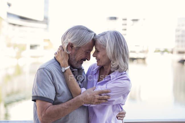 Старшая пара отдыхает в городе, целуется и обнимается — стоковое фото