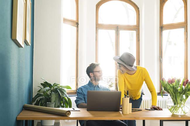 Casual imprenditore coppia in home office lavorando al computer portatile e sorridendo l'un l'altro — Foto stock