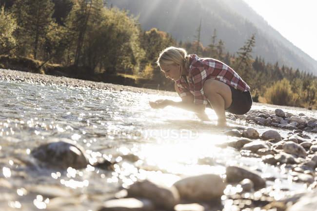 Austria, Alps, woman on a hiking trip having a break at a brook — Stock Photo