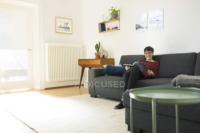 Casual short-haired woman relaxing on lounge couch in living room reading a magazine — Stock Photo