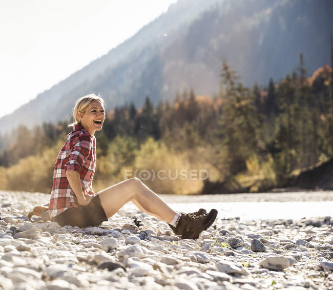 Austria, Alps, laughing woman on a hiking trip having a break at a brook — Stock Photo