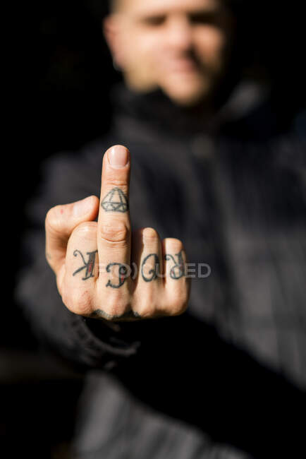 Tattooed man giving the finger, close-up — Stock Photo