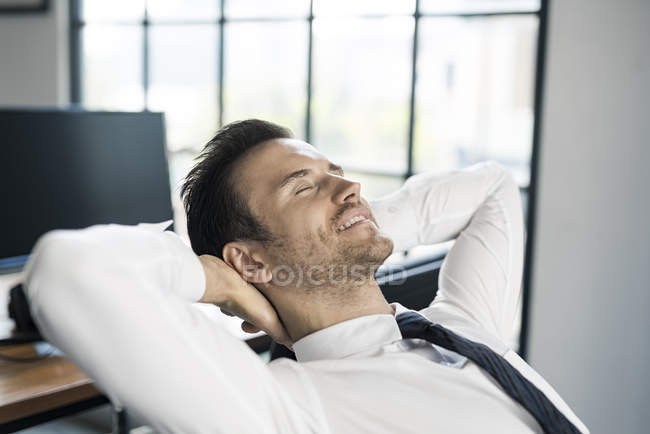 Smiling businessman in office leaning back — Stock Photo