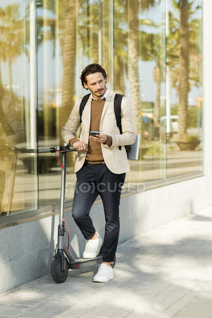 Man with E-Scooter and mobile phone in the city — Stock Photo