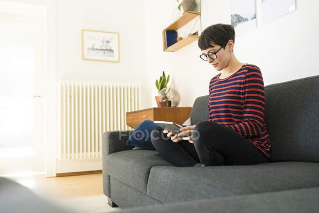 Незвичайна жінка з коротким волоссям відпочиває на вітальні дивані в сучасній вітальні за допомогою таблетки. — стокове фото