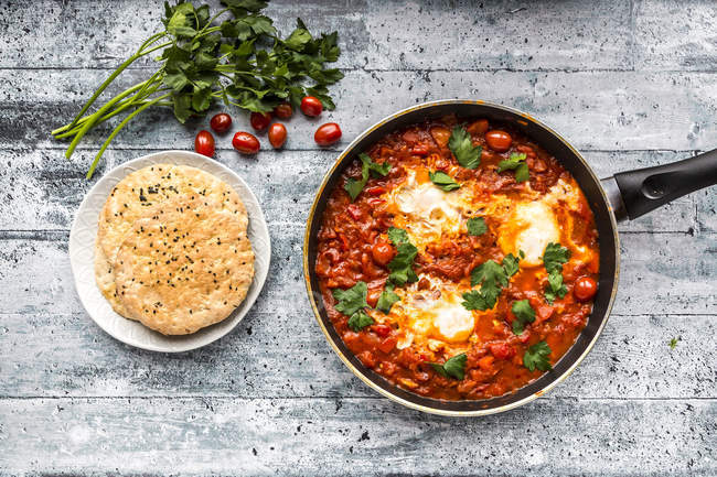 Shakshouka in pan and pita bread on plate — Stock Photo