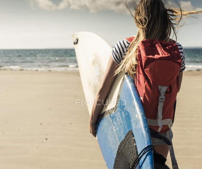 Junge Frau mit Rucksack, am Strand spazierend, mit Surfbrett — Stockfoto