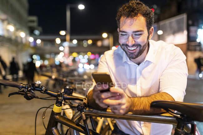 Щасливий чоловік, що вночі дивиться на телефон. — стокове фото