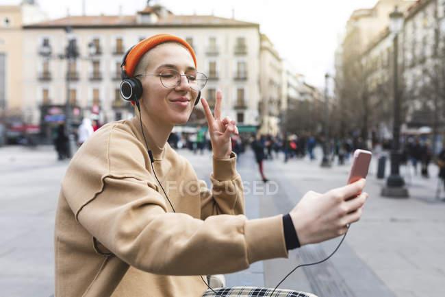 Junge Frau macht ein Selfie beim Musikhören und macht Friedensgeste mit der Hand — Stockfoto