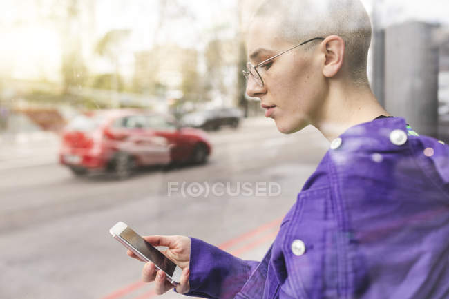 Young woman looking at her phone at the bus stop in the city — Stock Photo