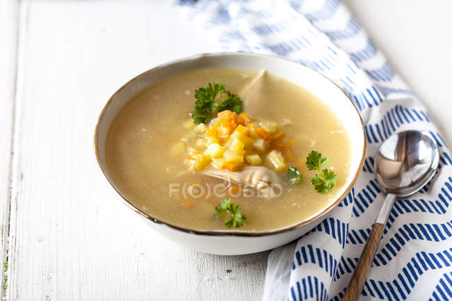 Bowl of homemade chicken stock with potatoes, carrots and parsley — Stock Photo