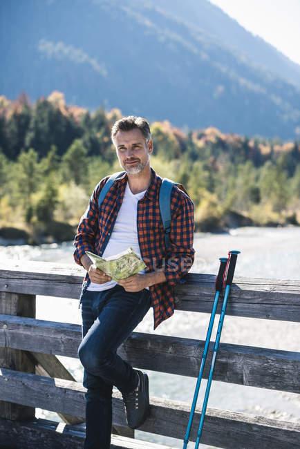 Austria, Alpes, hombre en un viaje de senderismo con mapa en un puente - foto de stock