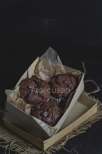 Chocolate muffins in a cardboard box — Stock Photo