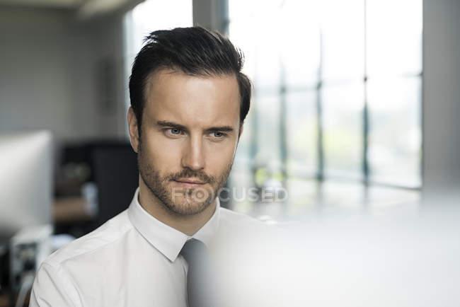 Uomo d'affari in ufficio che lavora al computer davanti alla finestra — Foto stock