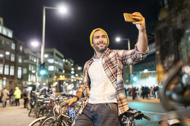 UK, London, man taking a selfie while commuting at night in the city — Stock Photo