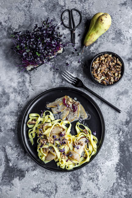 Tagliatelle with pear gorgonzola sauce, walnuts and red cress — Stock Photo