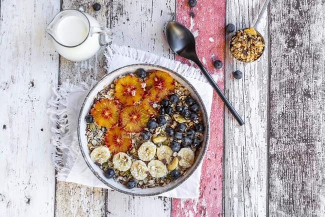 Крупи з бананом, чорницею, кров'яним апельсиновим, кокосовими пластівцями та молоком — стокове фото