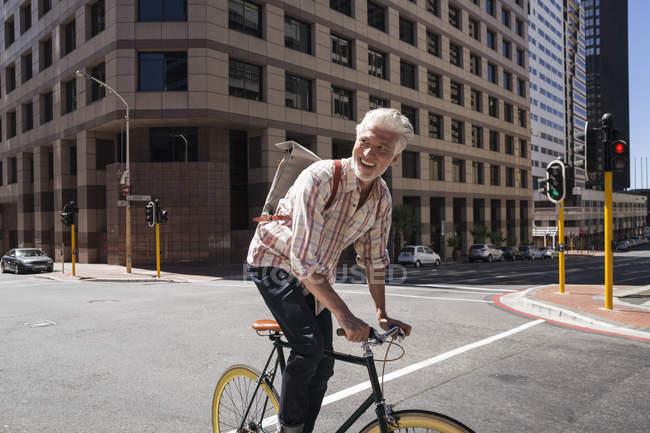 Uomo maturo in bicicletta in città — Foto stock