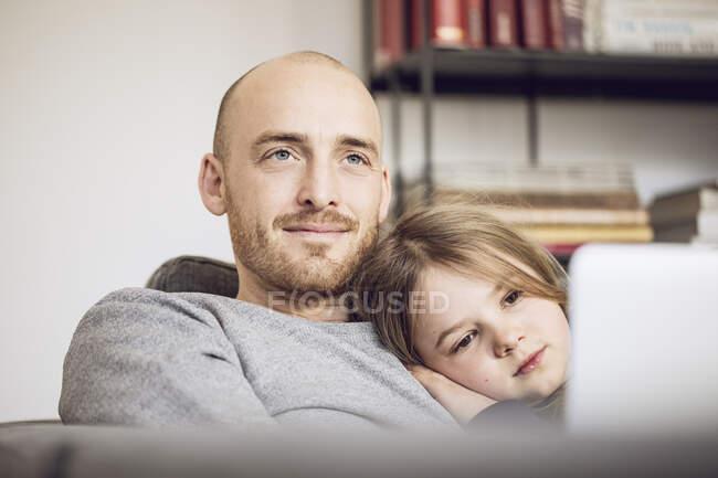 Батько з дочкою сидять на дивані з ноутбуком. — стокове фото