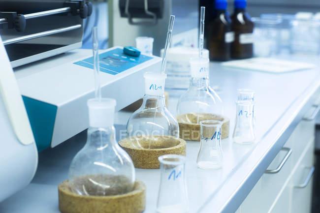 Vidrio de laboratorio sobre mesa en laboratorio - foto de stock