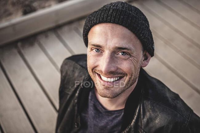 Ritratto di uomo sorridente con stoppia che indossa cappello lanoso — Foto stock