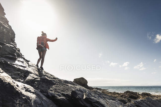 Young woman hiking on a rocky beach, taking pictures with her smartphone — Stock Photo