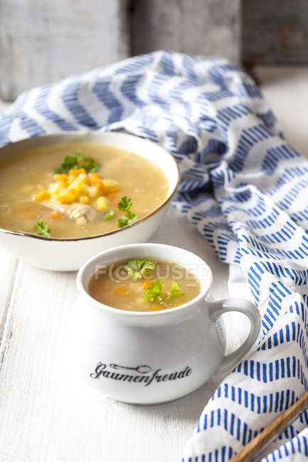 Bowls of homemade chicken stock with potatoes, carrots and parsley — Stock Photo