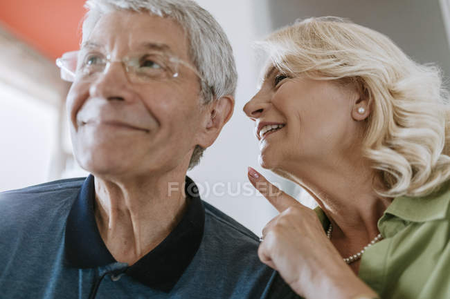 Senior woman talking to husband with hearing aid — Stock Photo