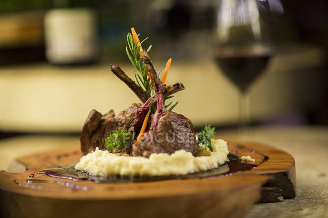 Garnished lamb chop on wooden serving plate — Photo de stock