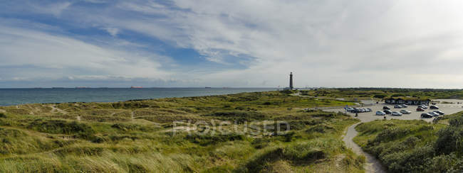 Denmark, Jutland, Skagen, Grenen, dune landscape with lighthouse in background — Stock Photo