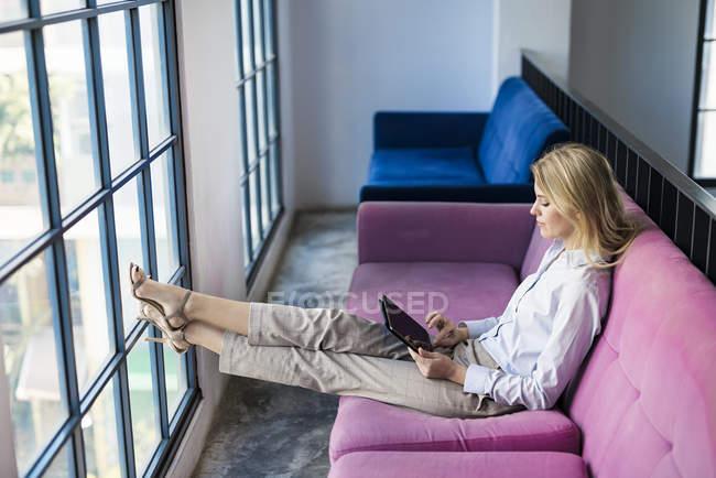 Блондинка-бизнесвумен сидит на фиолетовом диване у окна, используя планшет — стоковое фото