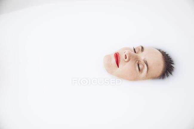 Красивая женщина, отдыхающая в молочной ванне — стоковое фото