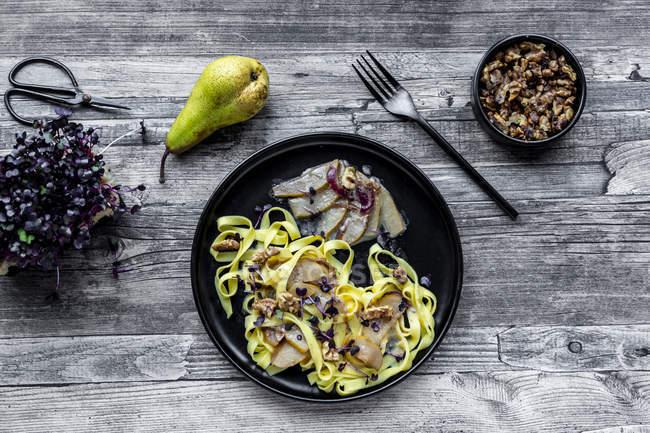 Tagliatelle con salsa gorgonzola de pera, nueces y cress rojo - foto de stock