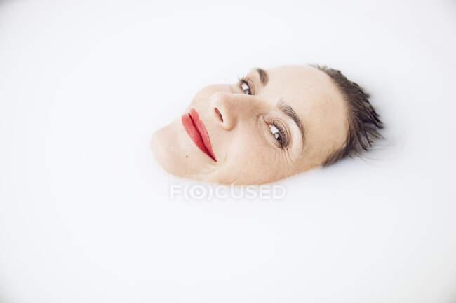 Bela mulher relaxando em um banho de leite — Fotografia de Stock